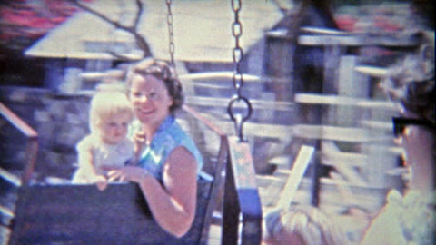 1962: Mom and baby enjoying dizzy hanging amusement park spinning ride at Knotts Footage