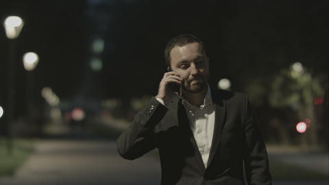 Businessman friendly talking by phone in city park in good mood Footage