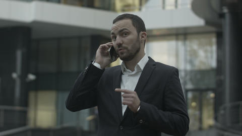 Displeased business man seriously talking by phone, standing outside the office Footage