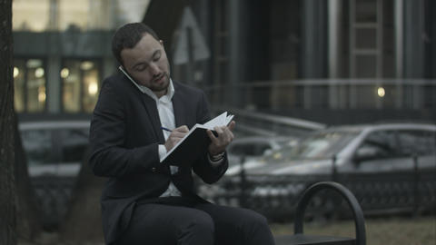 Young Bearded Businessman Talking By Phone And Writing In Diary, Working With No stock footage