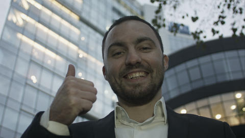 Portrait of young business man with beard smiling show tumb up, on office buildi Footage