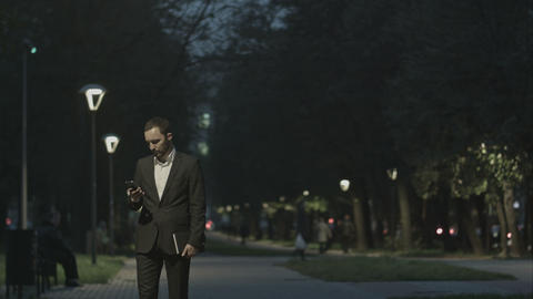 Portrait of handsome adult business man sending a text message while standing in Footage