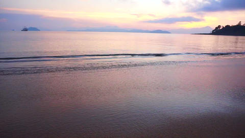 Video of beautiful sunrise sand beach and calm sea. Pink, purple and blue sky Footage