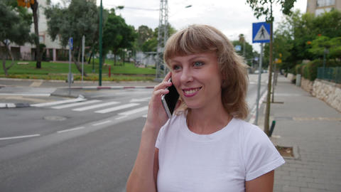 Attractive Girl Talking On Mobile Phone In The City. Dolly Shot Footage