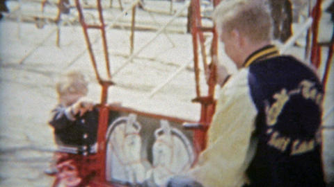 1964: Boy and dad swinging on playground toys and smiling hard Footage