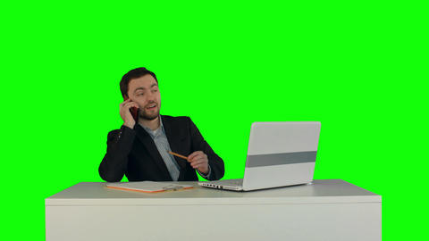Portrait of a smiling businessman talking on his smartphone while he working on  Footage