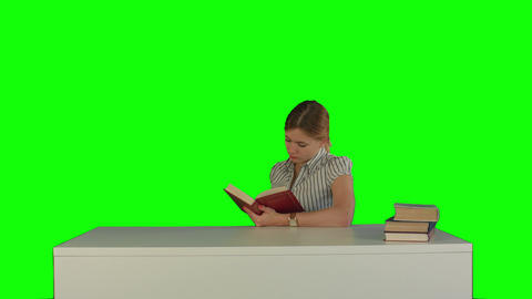 Female student reading a book for finding information on a Green Screen Footage
