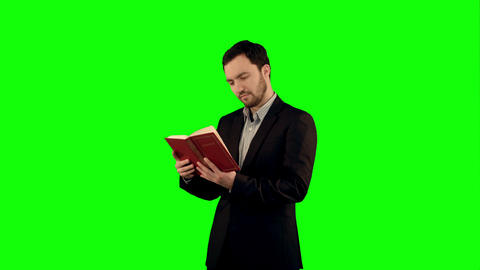 University student with book on laptop on a Green Screen, Chroma Key Footage