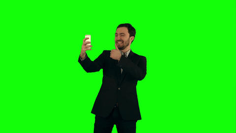 Young man taking a selfie photo with his smartphone on a Green Screen Footage