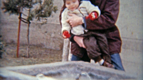 1964: Dad lifting up cute boy child up to water drinking fountain in public park Footage