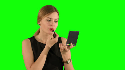 Woman with lipstick makeup looking herself in the mirror on a Green Screen Footage