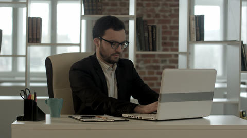 Businessman typing on his keyboard funny glasses Footage