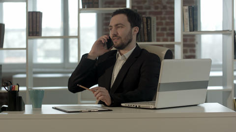 Successful young business man talking on cell phone at modern office Footage