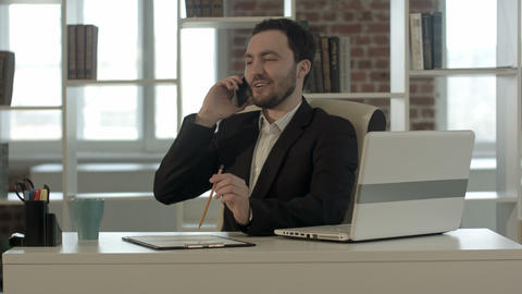 Happy smiling young man talking on mobile phone in office Footage