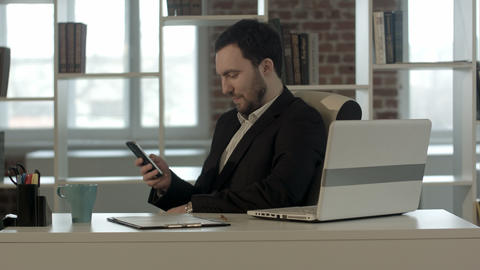 Happy people with businessman on the phone typing text message in office Footage