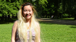 young attractive happy asian woman enjoys the sunny day in the park - smiles to  Footage