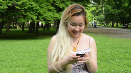 young attractive happy asian woman writes message in the park - close up Footage