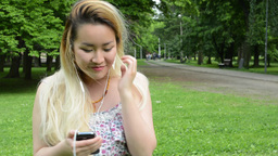 young attractive happy asian woman listens the music on smartphone in the park - Footage
