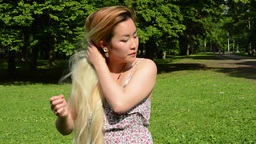 young attractive asian woman adjusts her clothes and hair in the park - style -  Footage