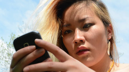 young asian attractive happy woman works with phone in outdoors - look from side Footage