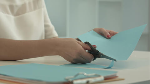 Girl is cutting color blue paper with scissors Footage