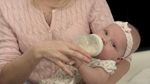 Bright mother feeding milk from bottle her adorable son at home Footage