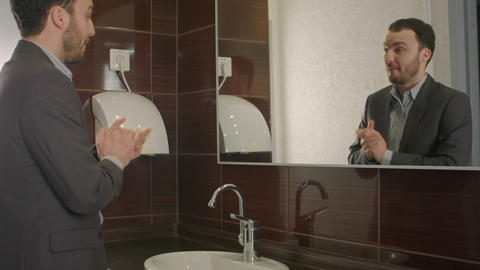 Businessman looking at himself in mirror to encourage and find himself confident Footage