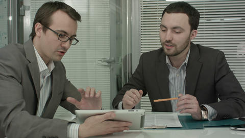 Image of two young businessmen using touchpad at meeting Footage