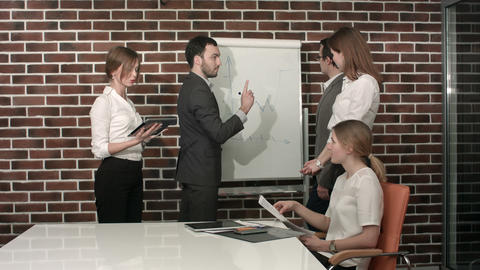Businessman giving a presentation on flipchart. Teamwork concept Footage