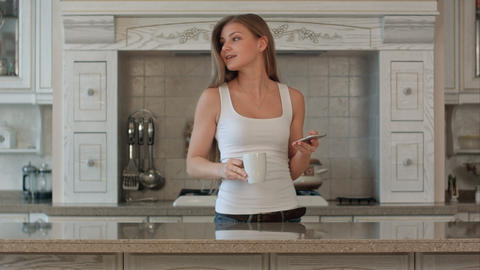 beautiful happy young woman with phone drinking coffee at home Footage