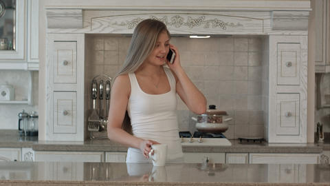 Young beautiful woman talking cell phone, drink coffee or tea in the kitchen, ha Footage