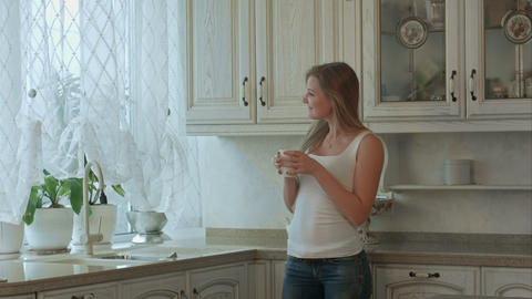 Beautiful girl drinks tea on kitchen at morning Footage