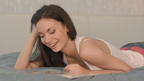 Young beautiful woman reading a magazine in bed Footage