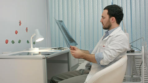 Male doctor or dentist looking at x-ray Footage