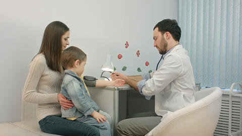 Doctor Measuring Blood Pressure Of A Child In Examination Room stock footage
