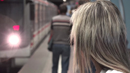 young attractive blonde woman waits for subway and looks around - arriving metro Footage