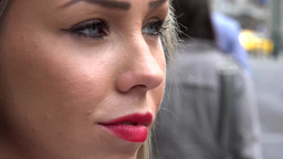 young attractive blonde woman looks around - urban street in the city with walki Footage