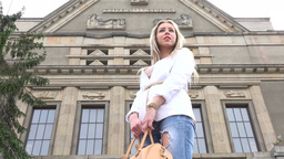 young attractive blonde woman looks around in front of university - shot from be Footage