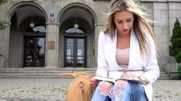 young attractive blonde woman reads book in front of university Footage