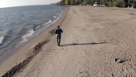 man runs on the seashore aerial view Live Action