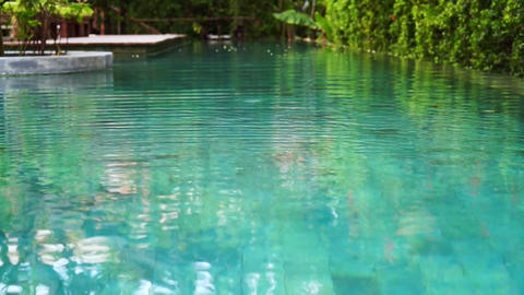 Point of view (POV) of relaxing in tropical resort swimming pool surrounded by n Footage
