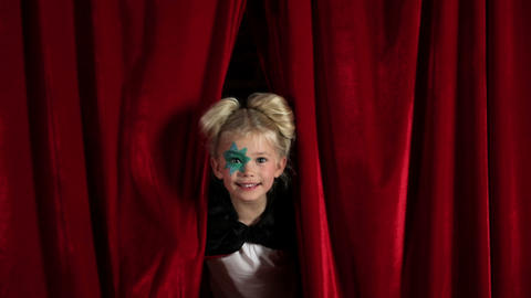 Young girl peeking through red curtain Stock Video Footage