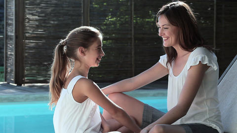 Mother and daughter talking by swimming pool Stock Video Footage