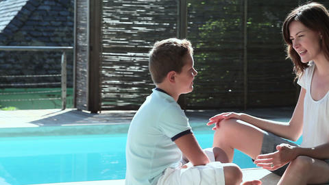 Mother and son talking by pool Stock Video Footage
