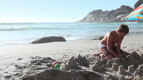 Boy and girl making sandcastles on beach Stock Video Footage