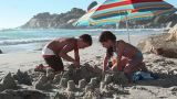 Boy and girl making sandcastles on beach Footage