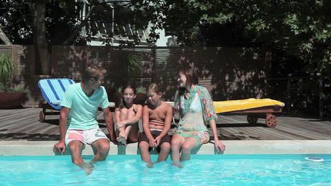 Family on edge of swimming pool Stock Video Footage