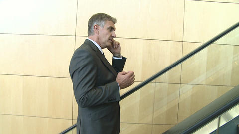 Businessman on escalator using cellphone Stock Video Footage