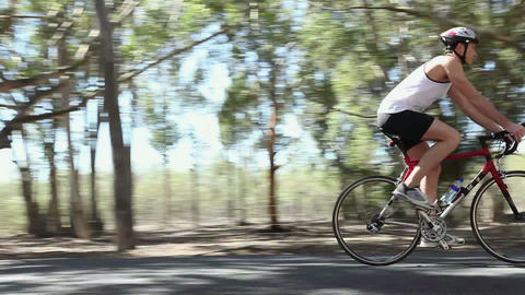 Young man cycling along road Stock Video Footage