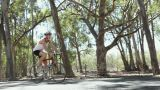 Young man cycling along road Footage